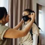 Mom putting mask on girl