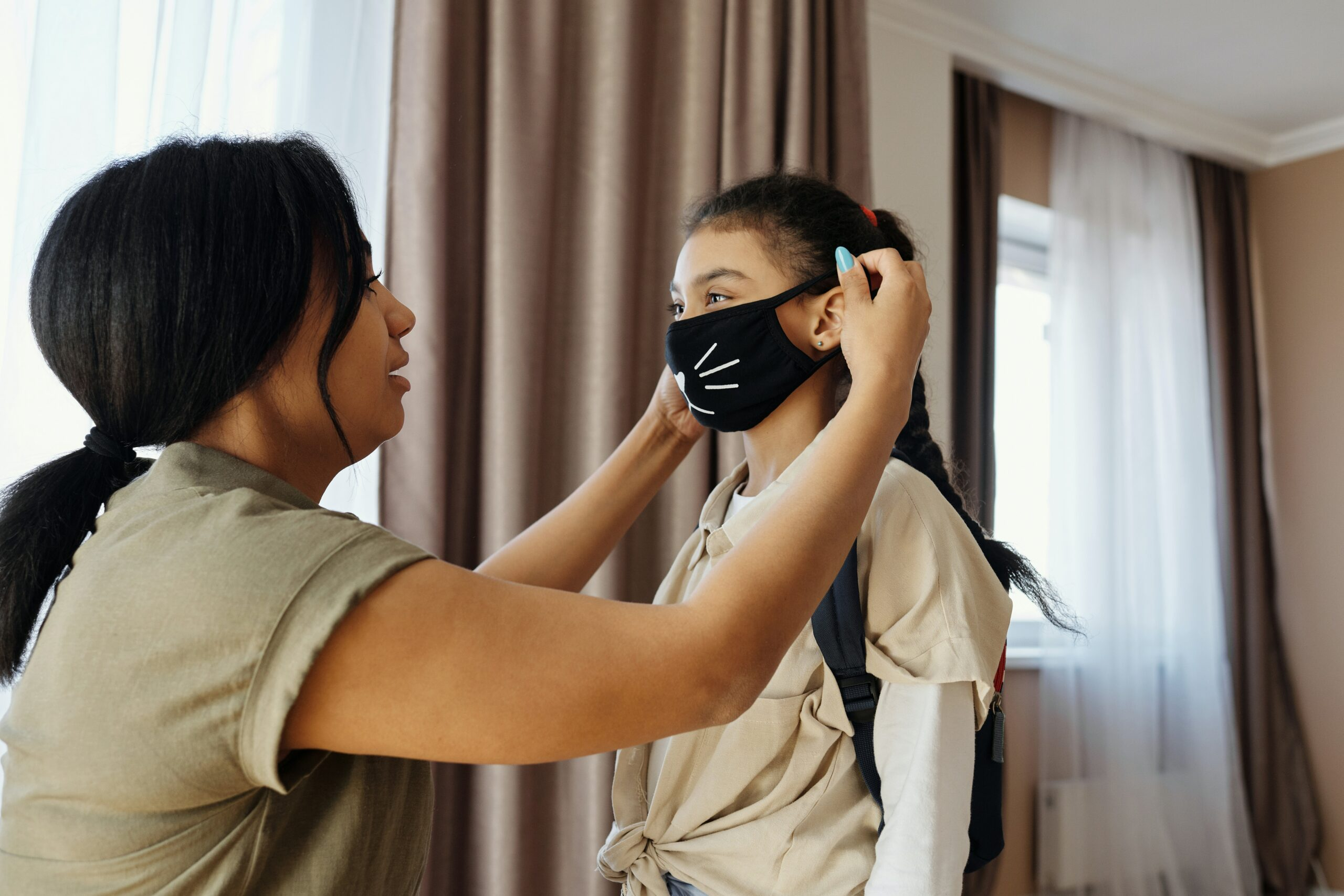 Mom putting mask on girl